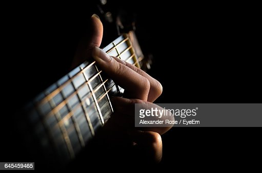 Cropped Image Of Hands Playing Guitar Against Black Background