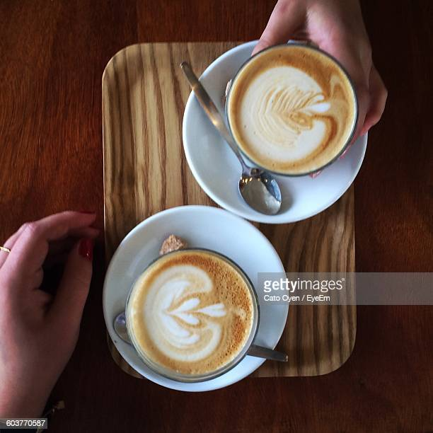 Cropped Image Of Hands Taking Coffee On Table