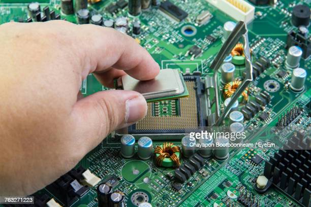 Cropped Image Of Hands Working On Mother Board