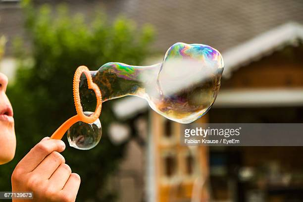 Cropped Image Of Kid Blowing Bubble In Back Yard