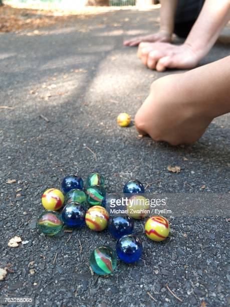 Cropped Image Of Male Friends Playing Marbles On Footpath