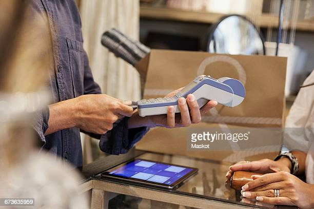 Cropped image of male owner using credit card reader for customer at store