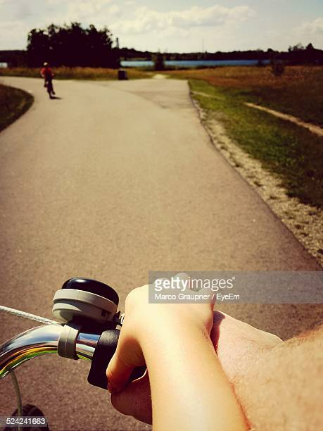 Cropped Image of Man Assisting Boy In Riding Bicycle On Road