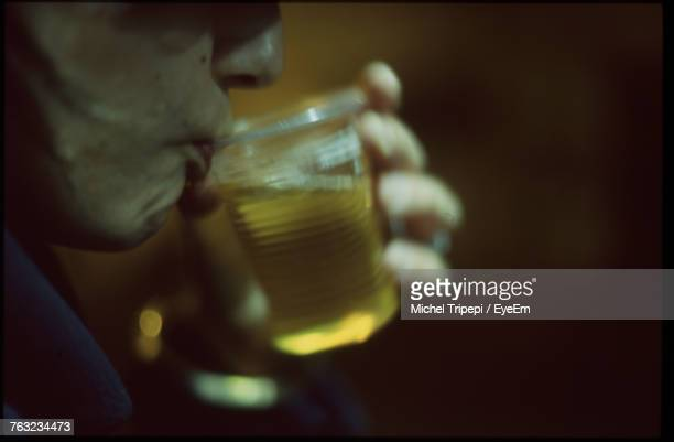 Cropped Image Of Man Drinking Beer In Glass At Night