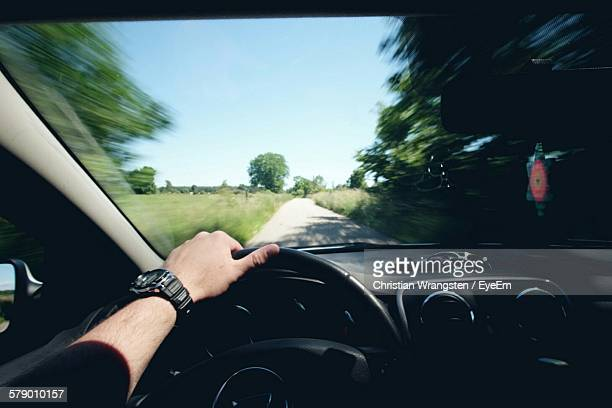 Cropped Image Of Man Driving Car On Road Amidst Trees