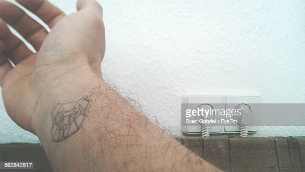 Cropped Image Of Man Hand With Tattoo At Home