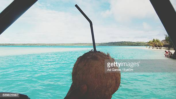 Cropped Image Of Man Holding Coconut At Beach Against Cloudy Sky