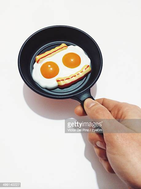Cropped image of man holding frying pan with artificial fried egg against white background