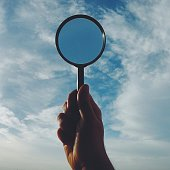 Cropped Image Of Man Holding Magnifying Glass Against Sky