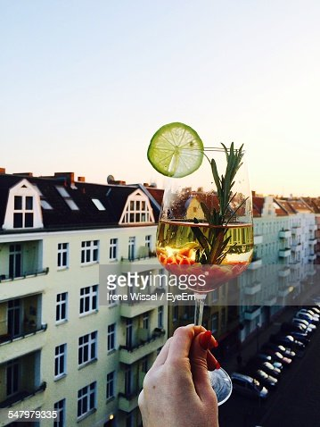 Cropped Image Of Man Holding Sangria By City Against Clear Sky