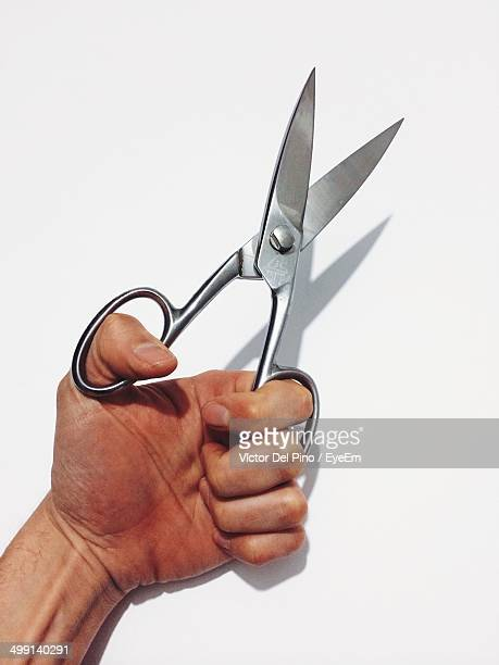 Cropped image of man holding silver scissors over white background