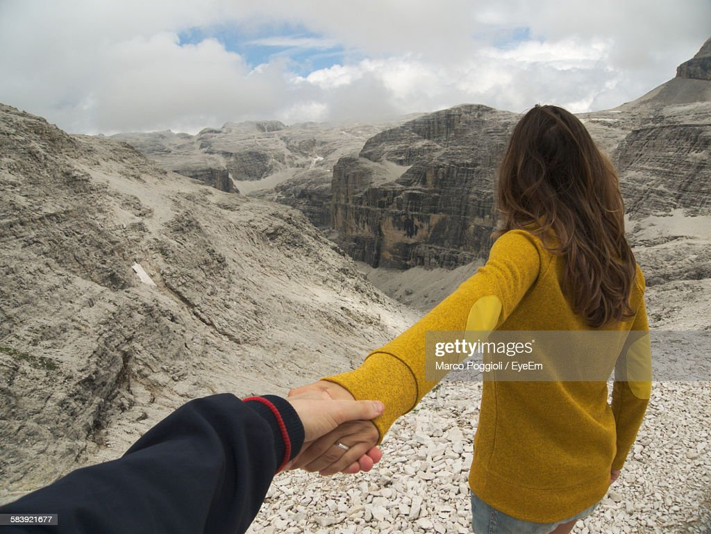 Cropped Image Of Man Holding Woman Hand By Rocky Mountains Against Sky