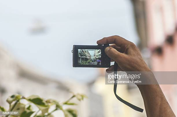 Cropped Image Of Man Photographing In City Through Digital Camera
