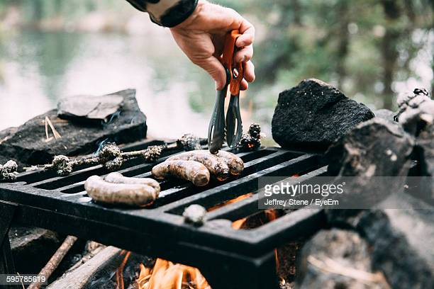 Cropped Image Of Man Roasting Sausages On Metal Grate At Campsite