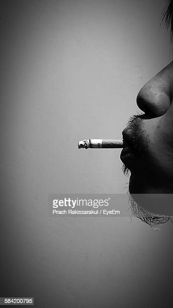 Cropped Image Of Man Smoking Cigarette Against Wall
