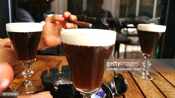 Cropped Image Of Man Smoking With Irish Coffee On Table At Cafe
