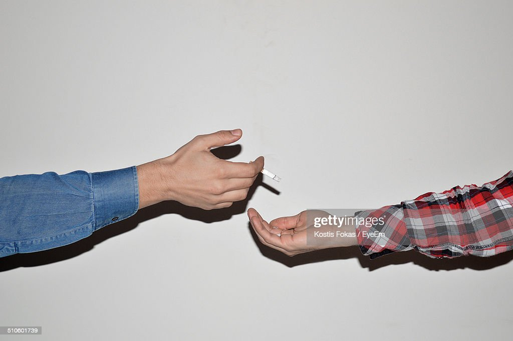 Cropped image of man throwing ashes of cigarette on male friend hand