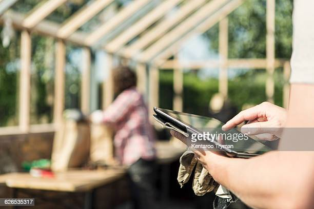 Cropped image of man using digital tablet while woman working in background at greenhouse