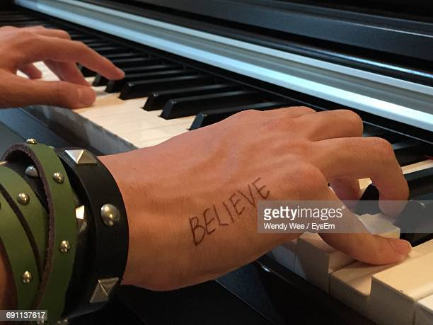 Cropped Image Of Man With Believe Text Tattoo Playing Piano
