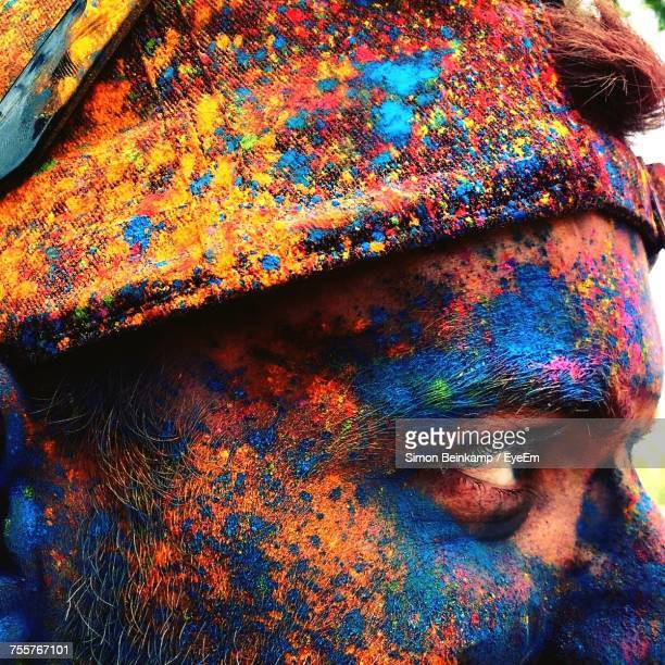 Cropped Image Of Man With Colorful Paint On Face During Festival