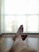 Cropped Image Of Man With Legs Crossed At Ankle Relaxing In Front Of French Window