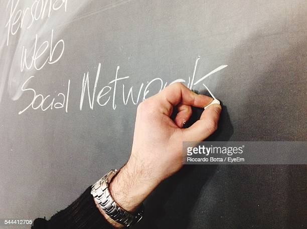 Cropped Image Of Man Writing On Board From Chalk