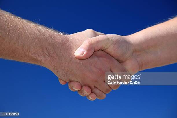 Cropped Image Of Men Handshaking Against Clear Blue Sky