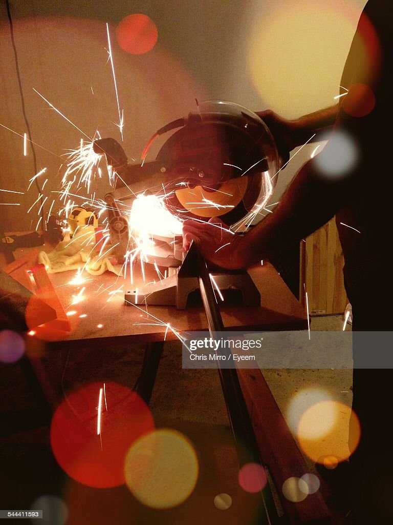 Cropped Image Of Metal Worker Using Circular Saw In Factory