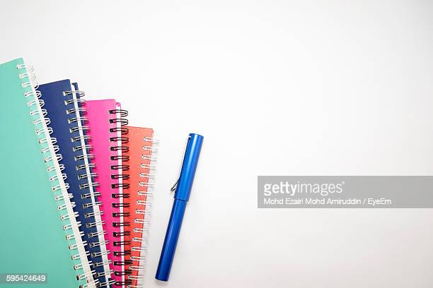 Cropped Image Of Multi Colored Books With Pen On White Background