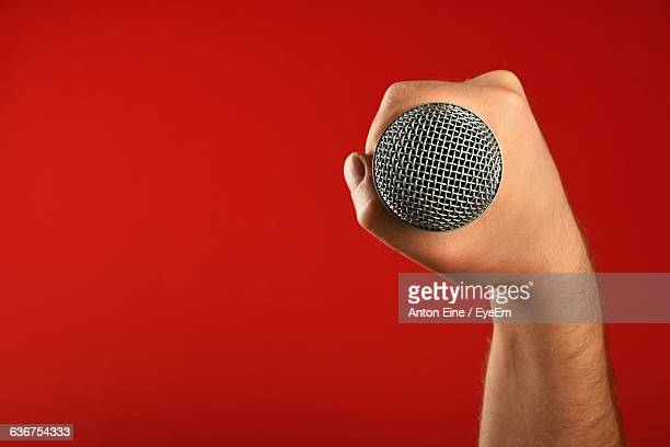 Cropped Image Of Musician Holding Microphone Against Red Background