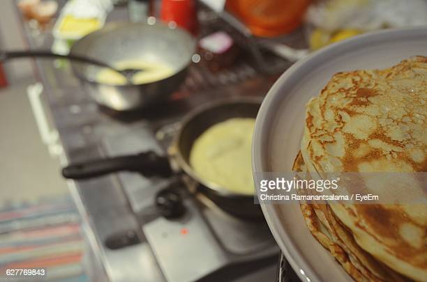 Cropped Image Of Pancakes In Plate Against Cooking Pans On Stove