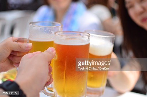 Cropped Image Of People Holding Beer Mugs : ストックフォト