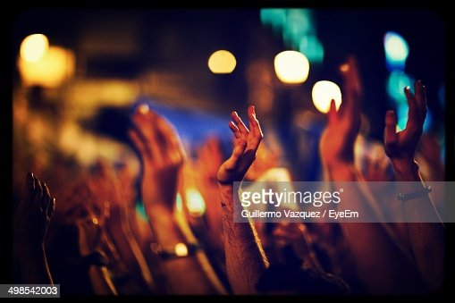 Cropped image of people with hands raised at concert hall