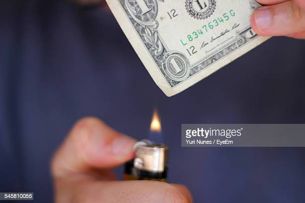 Cropped Image Of Person Burning Dollar Note With Lighter