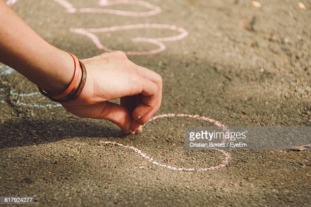 Cropped Image Of Person Drawing Heart Shape On Road