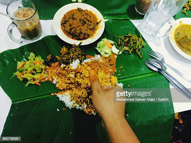 Cropped Image Of Person Eating Rice With Curry On Table