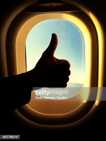 Cropped Image Of Person Gesturing Thumbs Up By Airplane Window