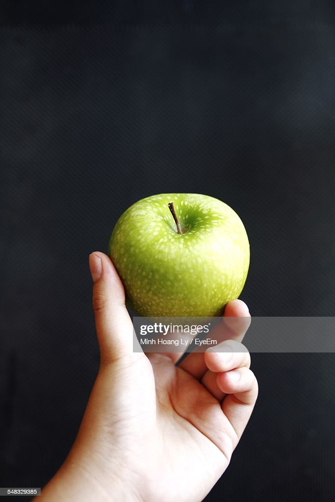 Cropped Image Of Person Holding Green Apple Against Black Background
