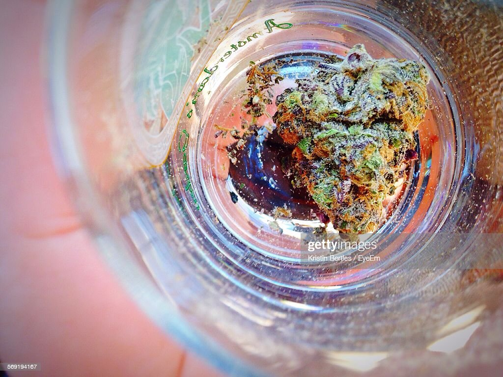 Cropped image of person holding marijuana in glass