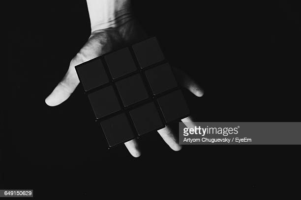 Cropped Image Of Person Holding Puzzle Cube On Black Background