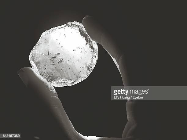 Cropped Image Of Person Holding Rosin Against Black Background