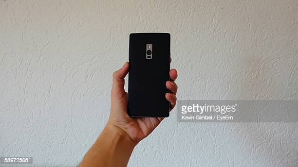 Cropped Image Of Person Holding Smart Phone Against Wall