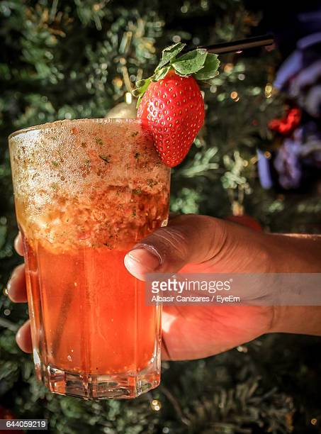 Cropped Image Of Person Holding Strawberry Mojito Glass