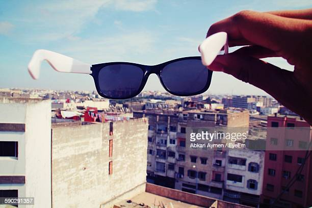 Cropped Image Of Person Holding Sunglasses By City Against Sky