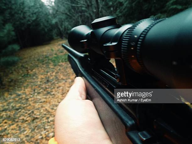 Cropped Image Of Person Hunting With Rifle In Forest
