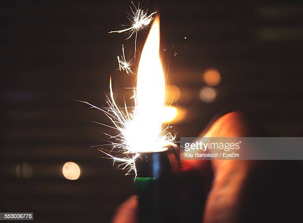 Cropped Image Of Person Igniting Cigarette Lighter