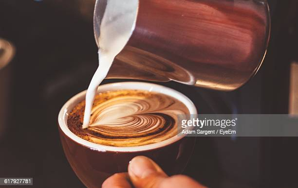 Cropped Image Of Person Pouring Milk In Coffee With Heart Froth