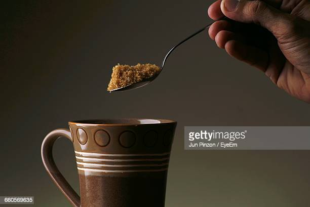 Cropped Image Of Person Putting Brown Sugar In Coffee Cup