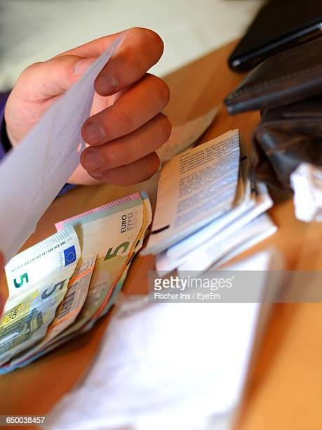 Cropped Image Of Person Reading Bill By Five Euro Banknotes On Table