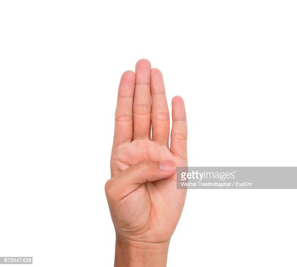 Cropped Image Of Person Showing Four Fingers Against White Background